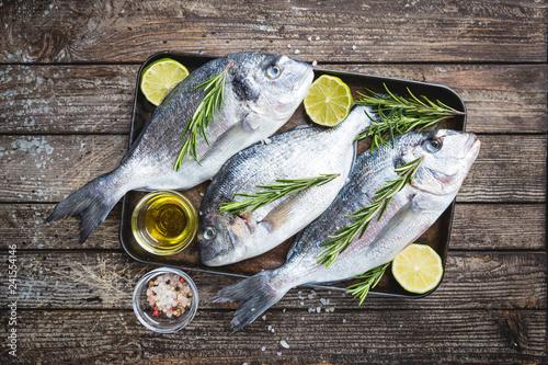 Leinwanddruck Bild Fresh raw Dorado or sea bream with spices, herbs, lemon and salt over wooden background Top view