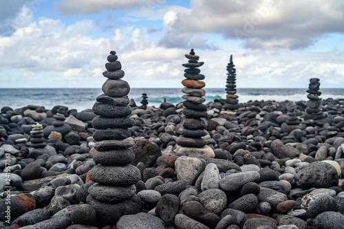 Many stone stacks on the beach near ocean - 241557361