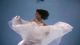 Charming woman floating underwater in a incredible white wedding dress, fluttering dress under the water. - 241560389