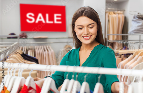 fashion sale, shopping and people concept - happy woman choosing clothes in clothing store