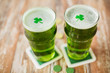 st patricks day, holidays and celebration concept - glasses of green beer with shamrock and gold coins on wooden table