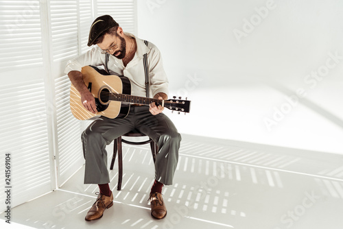 Leinwandbild Motiv handsome bearded man in cap sitting on chair and playing guitar near white room divider
