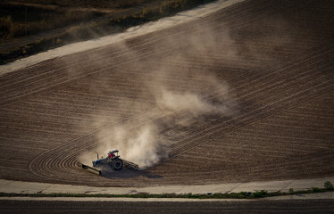 Tractor turning cassava roots, showing pollution caused from dust and contamination from this cash crop. © Philip