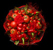 Unique gift handmade in the form of a bouquet consisting of a tomatoes, red peppers, bay leaves on a black background. Top view