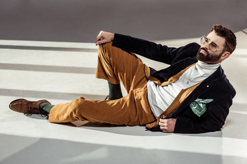 handsome stylish bearded man in glasses lying on floor