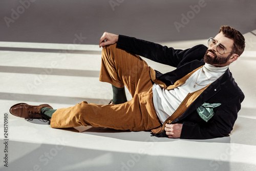 Leinwanddruck Bild handsome stylish bearded man in glasses lying on floor