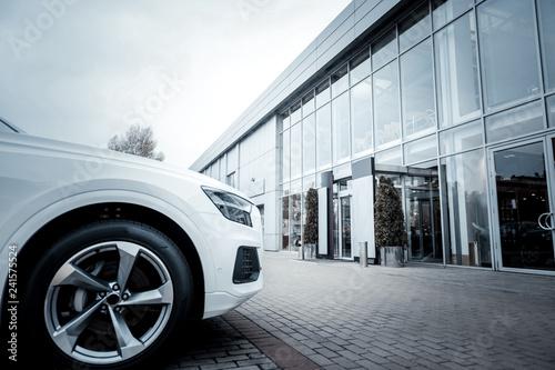 White passenger car standing outside in front of car salon - 241575524