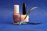 Nail polish and a nail clipper on a blue background - 241575944