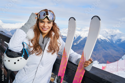 Portrait of beautiful woman with ski and ski suit in winter mountain. - 241576919