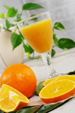 orange and glass of orange juice on white wooden table - 241580100
