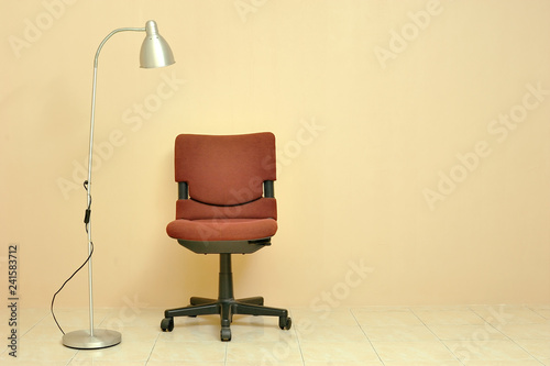 Red office chair with lamp over light beige wall background.