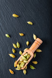 Exotic spices  Organic cardamom in bamboo scoop on black slate stone background - 241587176