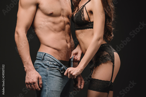 cropped view of woman undressing sexy shirtless man isolated on black - 241587532