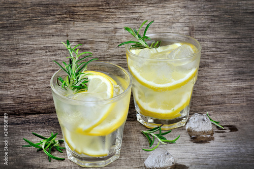 Fresh lemon with water in a glasses on table
