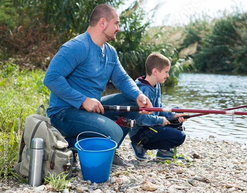 Leinwanddruck Bild Cheerful father and boy fishing with rods