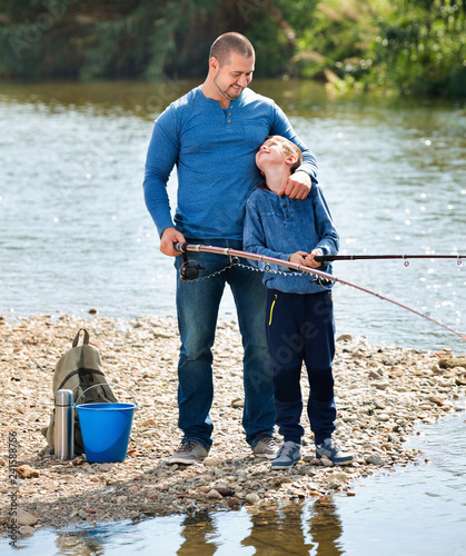 Leinwanddruck Bild Portrait of father and son fishing with rods