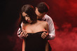 passionate man undressing his girlfriend in red smoky room