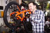 Worker mounts a bicycle saddle - 241591121