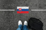 a man with a shoes and backpack is standing on asphalt next to flag of Slovakia and border