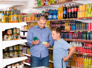 Happy family of father and teen son buying food products on shopping list in supermarket © JackF