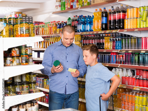 Happy family of father and teen son buying food products on shopping list in supermarket
