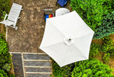 Vertical aerial photograph of a bright parasol on a terrace, taken from close up with the drone. - 241594375