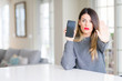 Young beautiful woman showing smartphone screen at home with open hand doing stop sign with serious and confident expression, defense gesture