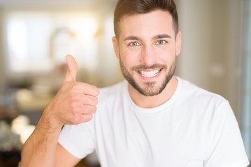 Young handsome man wearing casual white t-shirt at home doing happy thumbs up gesture with hand. Approving expression looking at the camera with showing success.