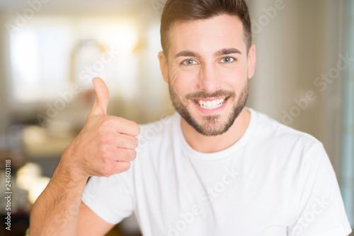 Leinwanddruck Bild Young handsome man wearing casual white t-shirt at home doing happy thumbs up gesture with hand. Approving expression looking at the camera with showing success.