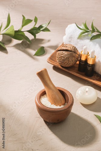 Burning candle in water. Spa setting with salt and pebbles on wooden background