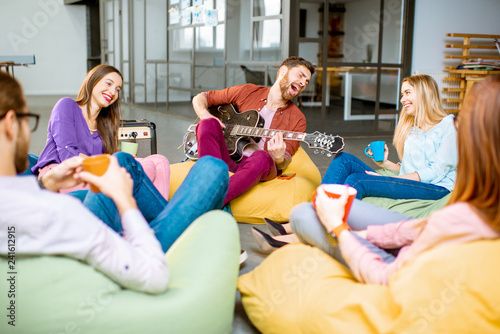 Group of a young coworkers having fun sitting on the colorful poufs playing guitar during the coffee break in the office