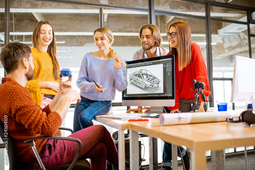 Group of young creative coworkers designing a car model at the working place with computers in the modern office interior
