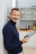 Leinwanddruck Bild - Smiling man with tablet pc, looking at camera