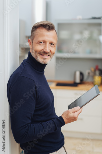 Leinwanddruck Bild Smiling man with tablet pc, looking at camera
