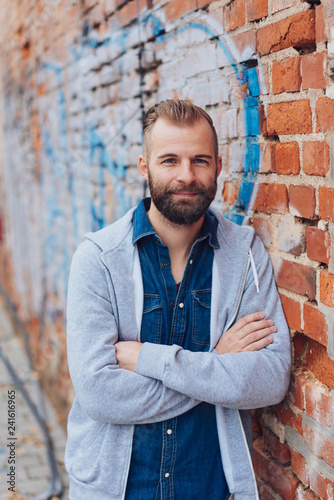 Young handsome man leaning on brick wall