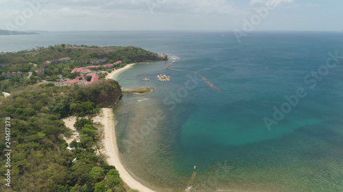 Aerial view of coast with beach, hotels. Philippines, Luzon. Coast ocean with tropical beach, turquoise water. Tropical landscape in Asia.