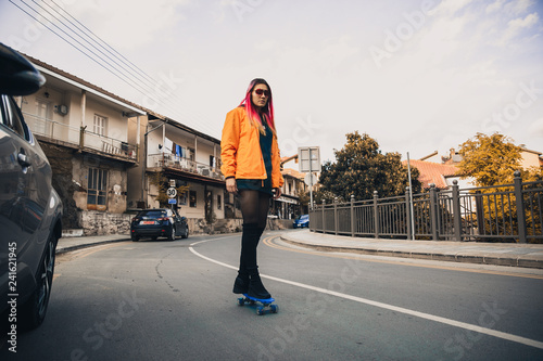 obraz lub plakat Girl on a skateboard on the road