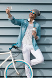 modern young guy with casual clothes, hat and glasses on bicycle - 241622974