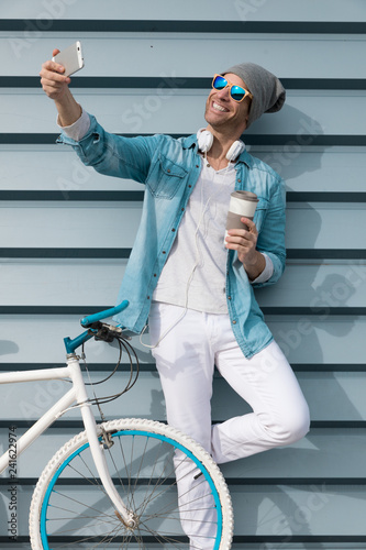 modern young guy with casual clothes, hat and glasses on bicycle