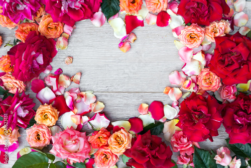 Frame heart made of rose flowers on wooden background for Valentines day. Flat lay, copy space - 241623131