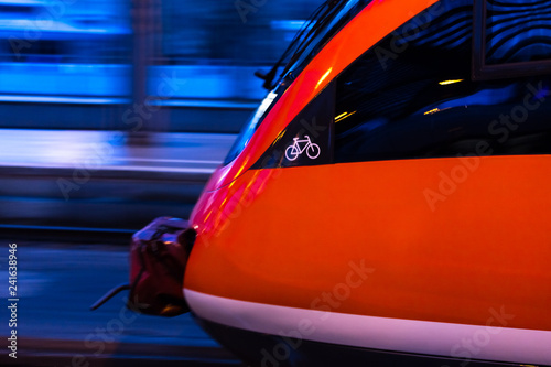 red passenger train in the evening