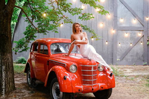 Girl in a white dress with a red old car - 241647785