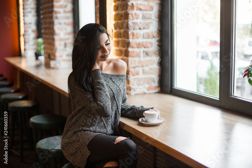 Beautiful girl drinks coffee, sitting in a cozy cafe. - 241660359