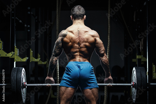 Muscular man bodybuilder training in gym and posing. Fit muscle guy workout with weights and barbell