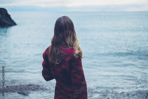 Young woman on the beach looking at the sea