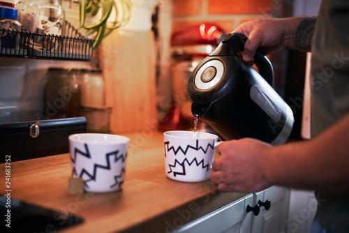 Man preparing coffee or tea in kitchen