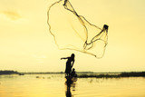 silhouette of fisher man throwing dip net fishing at lake with mountain and blue sky background. - 241686738