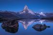 Leinwanddruck Bild - The famous Matterhorn and the moon reflected in the Stellisee  before dawn. Zermatt, Switzerland.