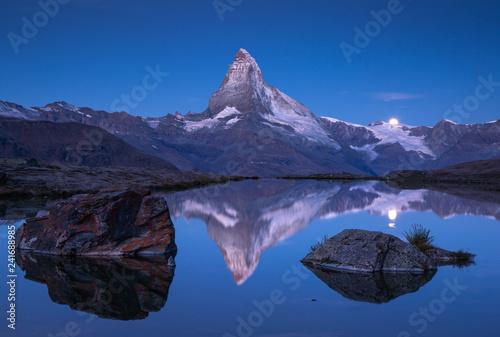 Leinwanddruck Bild The famous Matterhorn and the moon reflected in the Stellisee  before dawn. Zermatt, Switzerland.