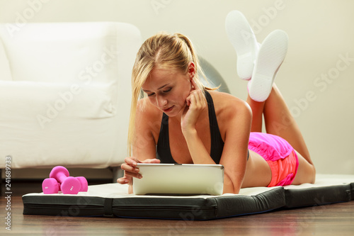 Fit woman lying on floor with tablet pc - 241689733